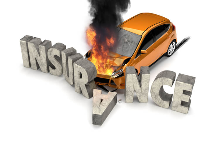 Orange compact car on fire crashed into large stone INSURANCE letters claim concept