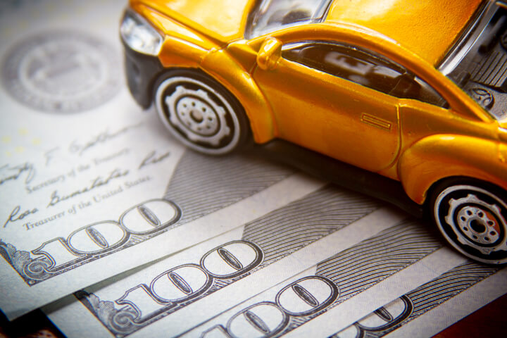 Toy car on top of fanned 100 dollar bills car insurance cost concept photo