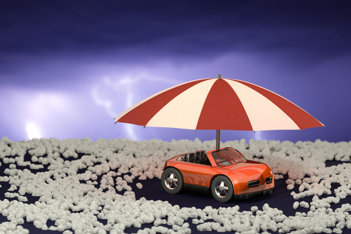 Toy car under umbrella surrounded by hail stones with lightning in sky after a hail storm