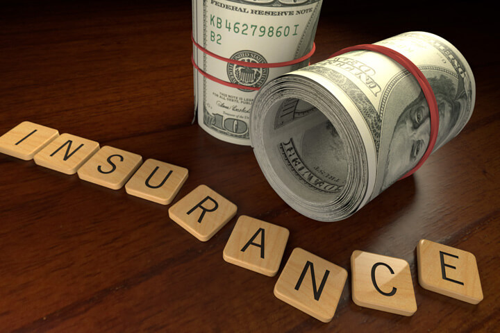 Wooden letters spell insurance with two rolls of 100 dollar bills