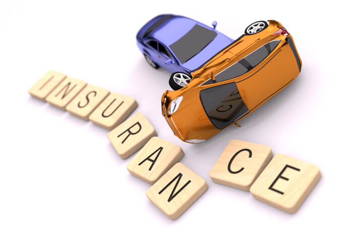 Two car collision displacing wood letters spelling insurance isolated on white