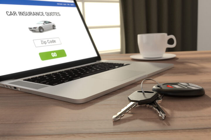 Laptop showing car insurance quotes website with coffee and keys on desk