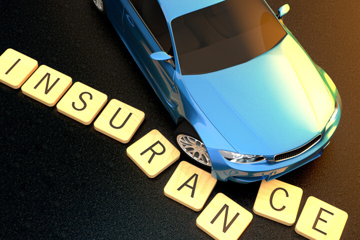 Concept image of blue car at sunset skidding through insurance letters on asphalt
