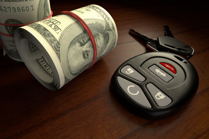 Cost of insurance concept showing two rolls of money next to car keys on desk
