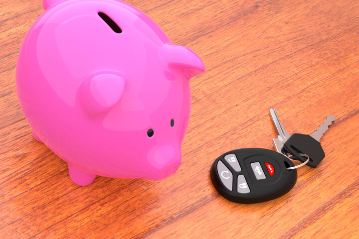 Pink piggy bank on desk next to car keys and key fob