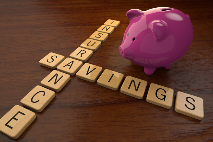 Insurance savings spelled out in wooden letters next to pink piggy bank on desk