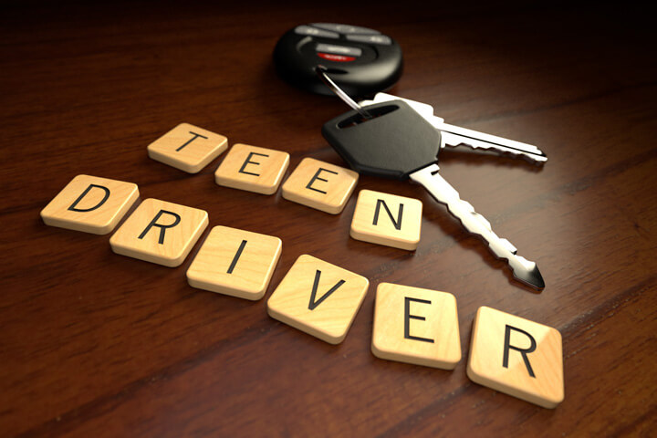 Teen driver in wooden letters with car keys on wooden desk