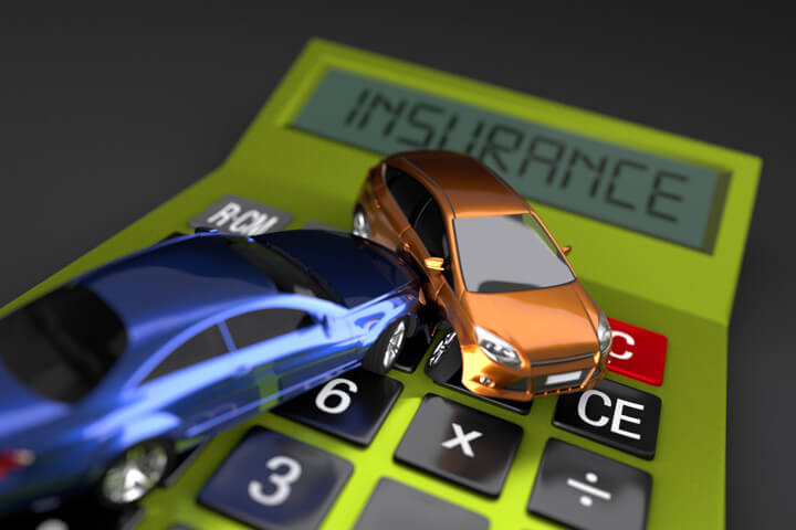 Two cars in accident on bright green calculator displaying insurance on darker background