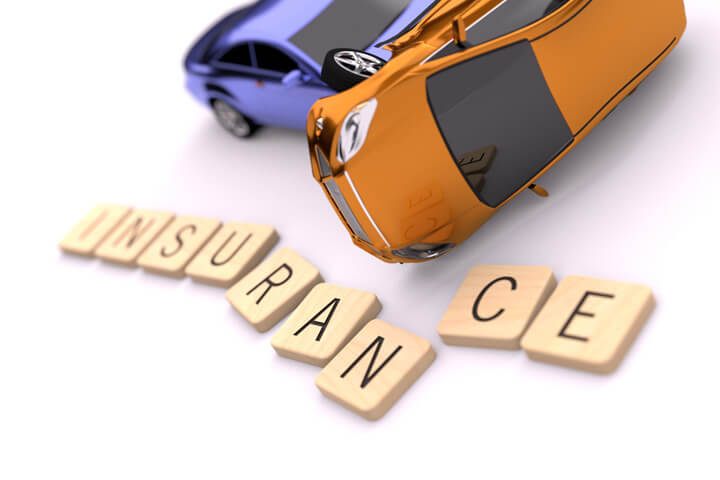 Two car rollover accident on white background with displaced wooden insurance letters