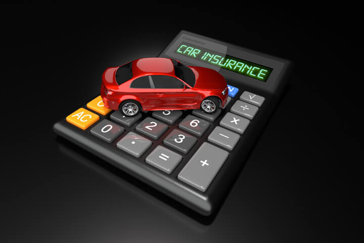 Red car sitting on calculator with LCD words Car Insurance