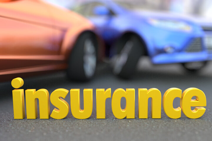 Two car accident blurred in background with word insurance in focus in foreground