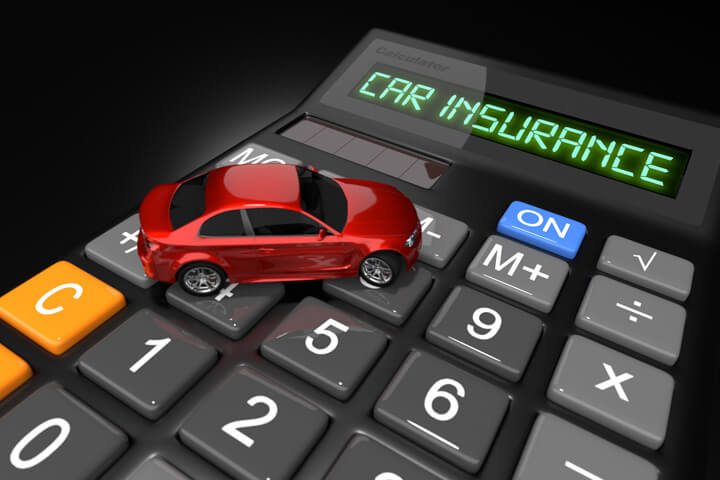 Small red toy car on car insurance calculator on dark background