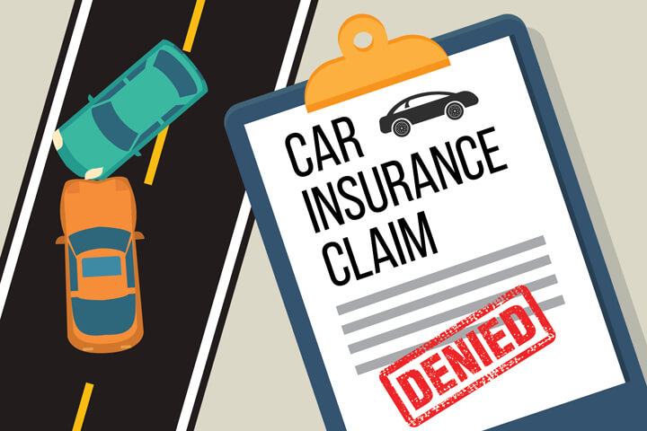 Two cars crashed on street with car insurance claim on clipboard with large DENIED stamp