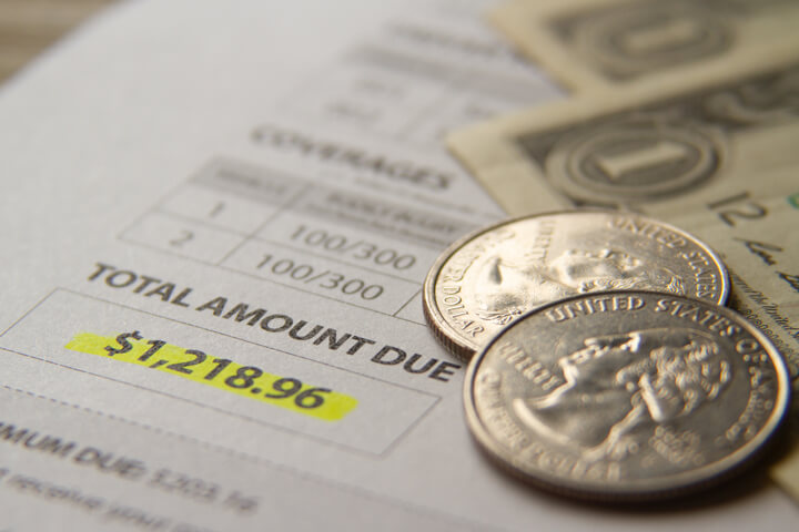 Car insurance billing notice with dollar bills and quarters