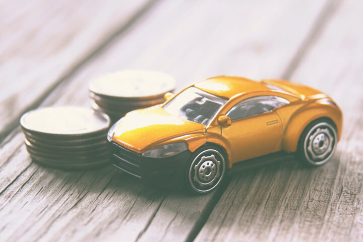 Small toy car on wood planks with stacks of coins