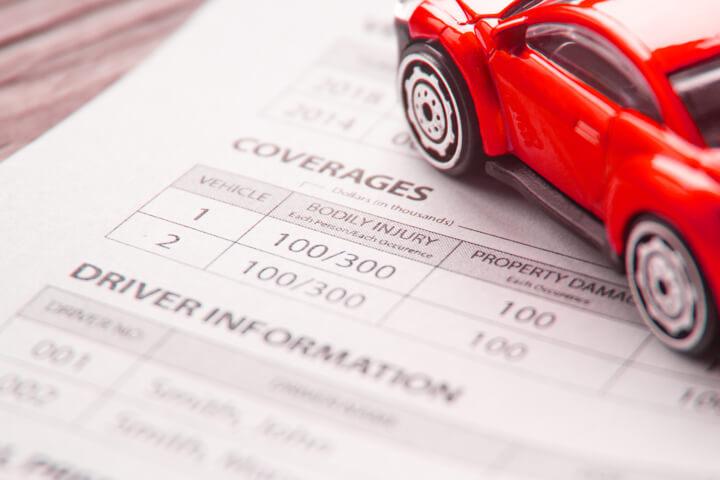 Auto insurance policy showing coverages and driver information with red toy car