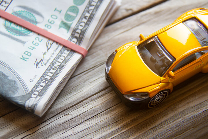 Yellow toy car next to folded 100 dollar bills car insurance or automotive costs concept photo