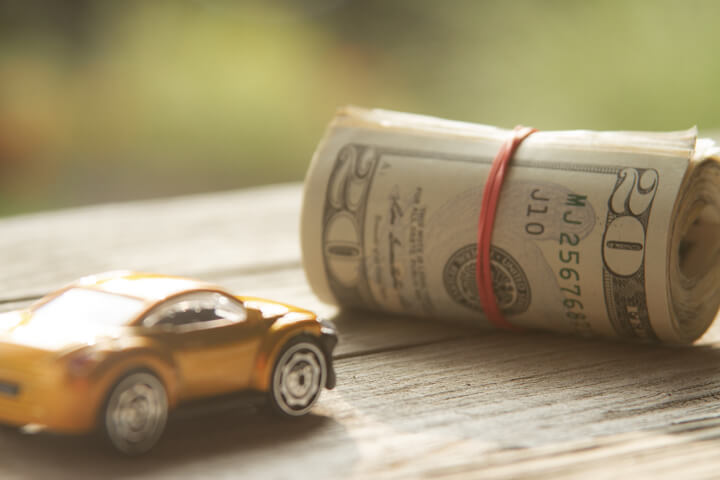 Small toy car next to roll of money wrapped in rubber bands