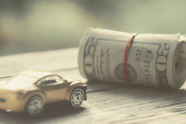Vintage photo of small toy car next to roll of money wrapped in rubber bands