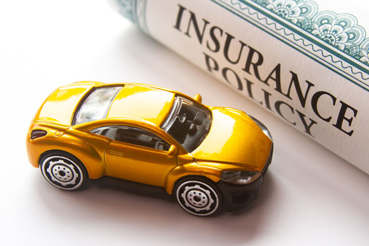 Yellow toy car next to rolled up insurance policy certificate