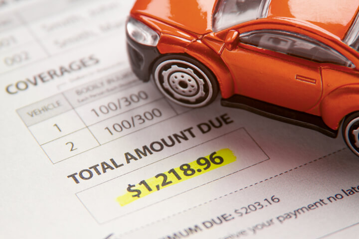 Toy car sitting on car insurance bill with payment due highlighted in yellow