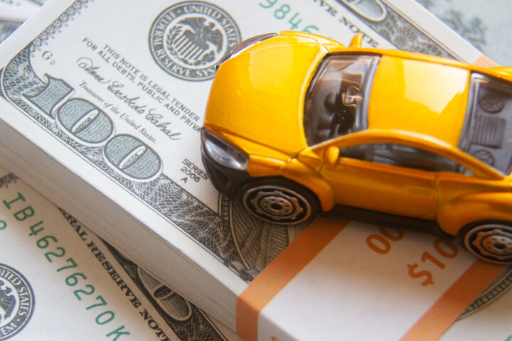 Yellow toy car on top of $10,000 cash bundle car insurance or automotive cost concept photo