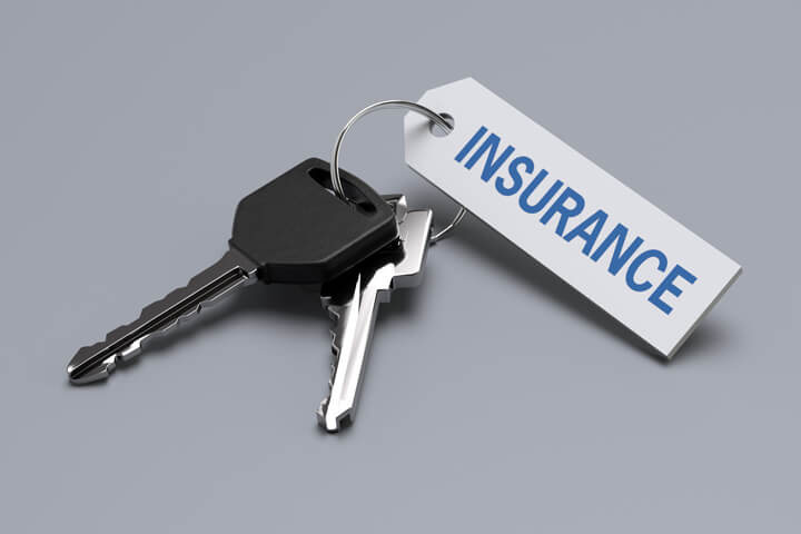 Car keys with insurance tag isolated on gray background