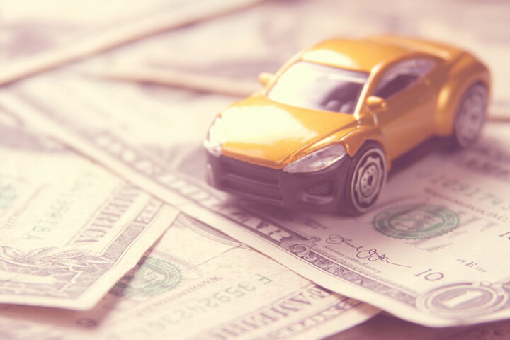 Small car on scattered dollar bills illustrating automotive cost or auto insurance cost
