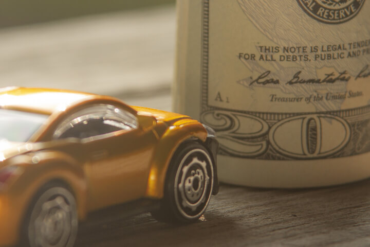 Small yellow car next to upright money roll on wood background