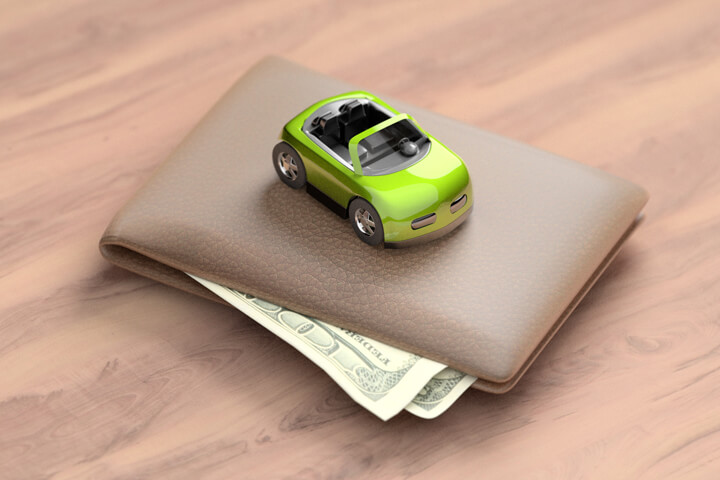 Green toy car sitting on top of wallet with corners of bills sticking out from wallet on wood table
