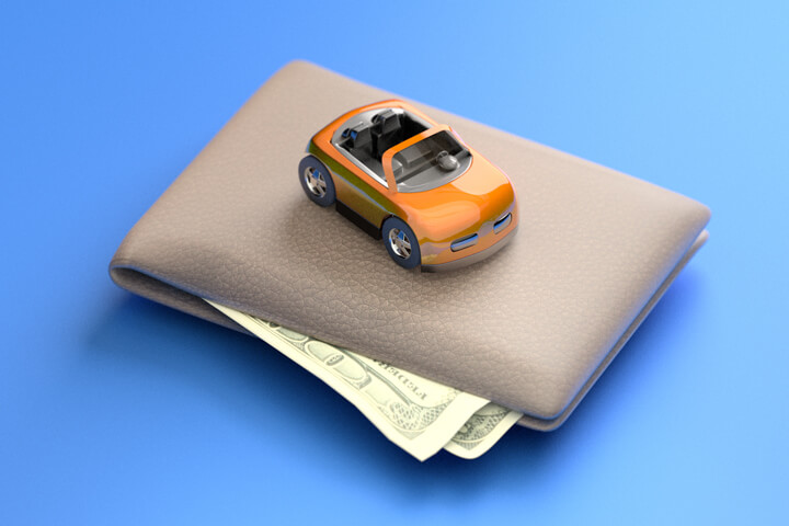 Toy car sitting on top of wallet with corners of bills sticking out from wallet blue background