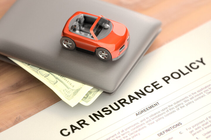 Toy car sitting on top of wallet with car insurance policy papers on wood table