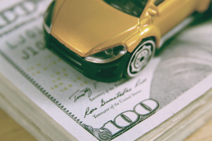 Toy car on stack of one hundred dollar bills