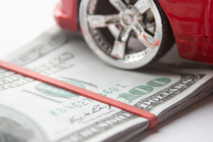 Close view of chrome car wheel and tire resting on folded 100 dollar bills with rubber band