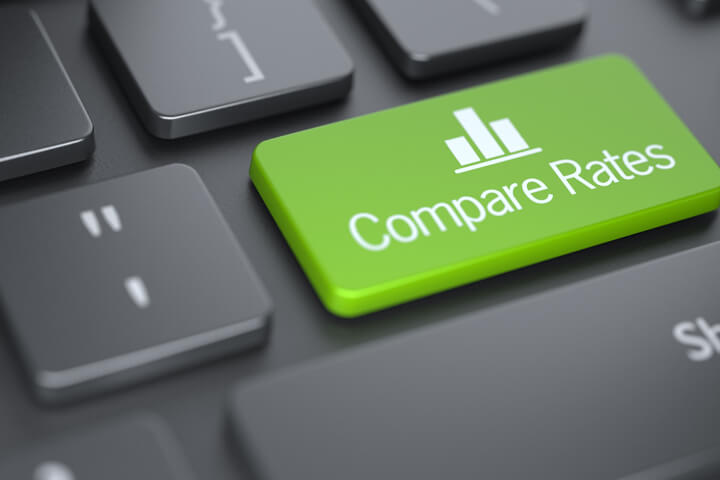 Dark laptop keyboard with green Compare Rates key with chart icon concept for comparing car insurance rates online
