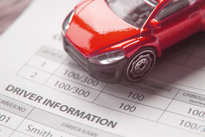 Toy car on top of auto insurance policy showing driver information