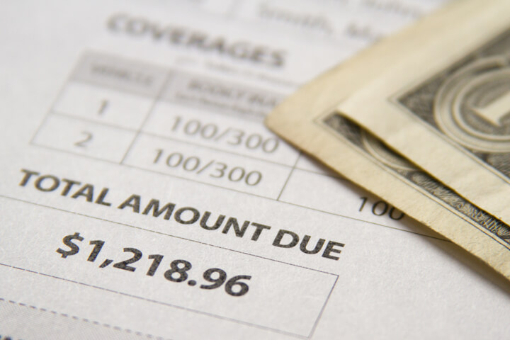 Auto insurance bill showing amount due with two dollar bills