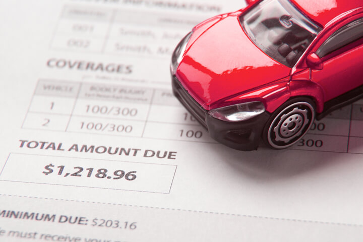 Auto insurance bill showing total amount due with small red toy car