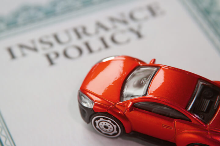 Red car on an insurance policy certificate with focus on the car and short depth of field