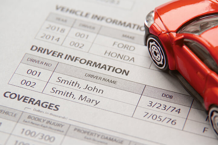 Car insurance policy showing vehicle and driver information with small red toy car