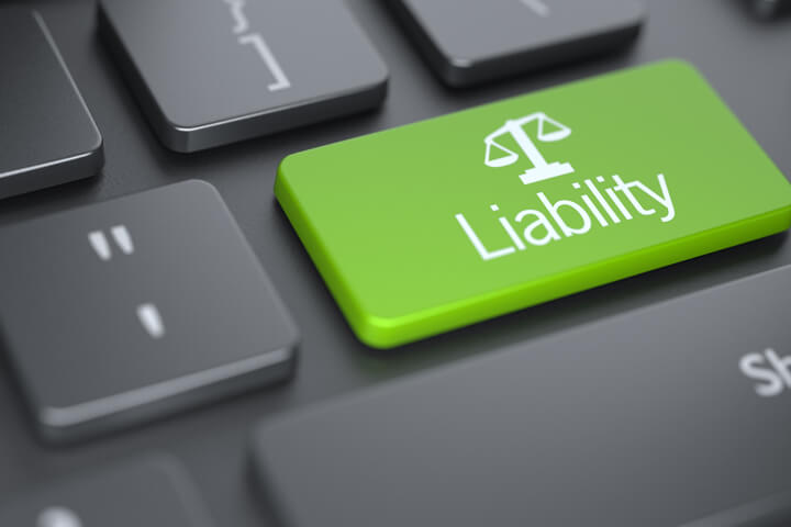 Dark laptop keyboard with green Liability key with legal scale icon concept for finding or researching liability insurance online