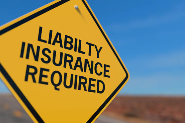 Yellow road sign reading Liability Insurance Required symbolizing mandatory state insurance liability laws