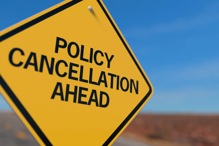 Yellow road sign reading Policy Cancellation Ahead concept for insurance policy cancellation