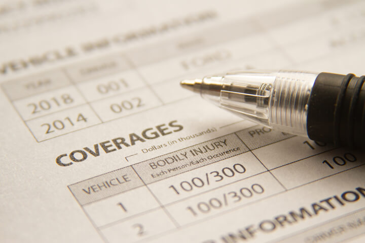 Car insurance policy showing coverages with ink pen