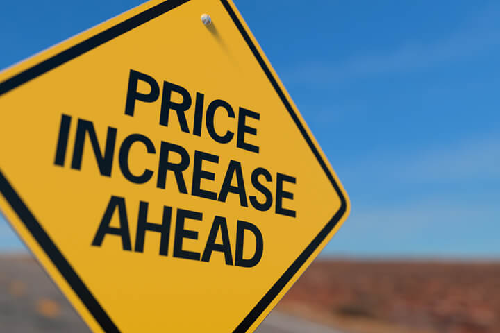 Yellow road sign reading Price Increase Ahead concept for upcoming insurance rate increase