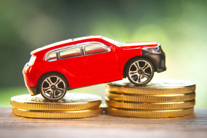 Red toy car on two increasing stacks of gold coins with blurred nature background