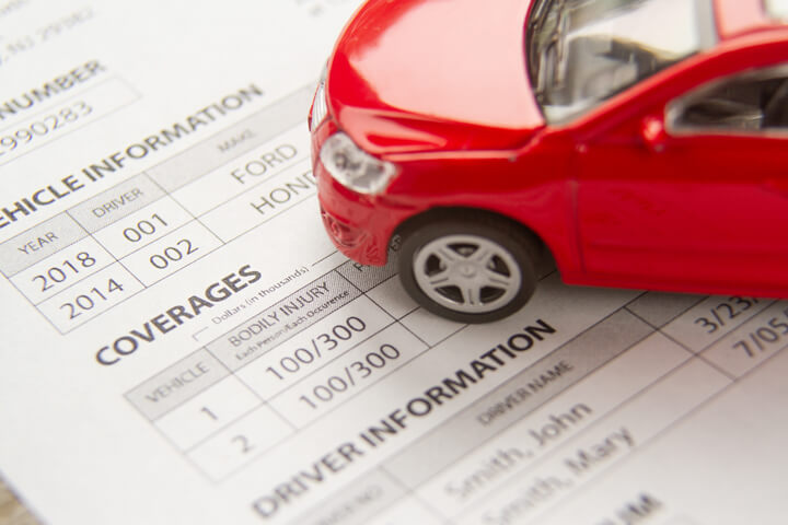 Red toy car on a car insurance policy showing vehicle and driver information and coverages