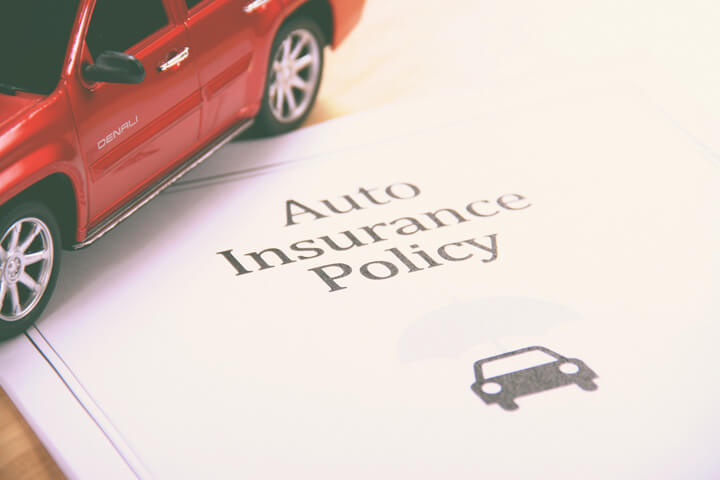Auto insurance policy with red SUV sitting on it