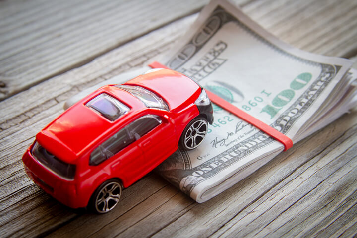 Red SUV climbing folded 100 dollar bills car insurance or automotive cost concept photo