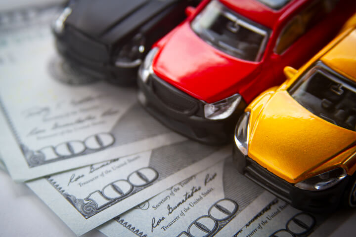 Photo of black, yellow, and red toy cars on fanned out 100 dollar bills